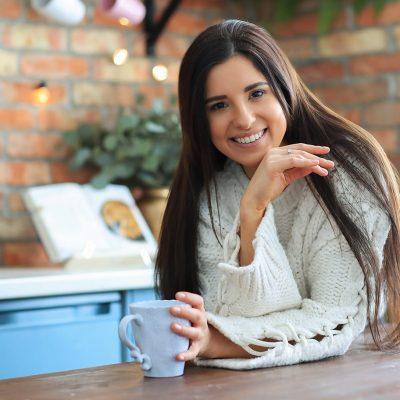 beautiful-young-woman-drinking-coffee-tea-kitchen